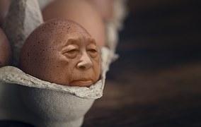紙パックに入った卵のひとつが人面になっている