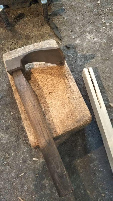 線を切り抜いた鍬の柄と木の台の上にある前チョウナ