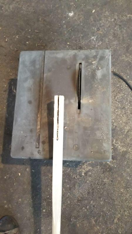 電動ノコギリの上にある黒い線を切り抜いた鍬の柄