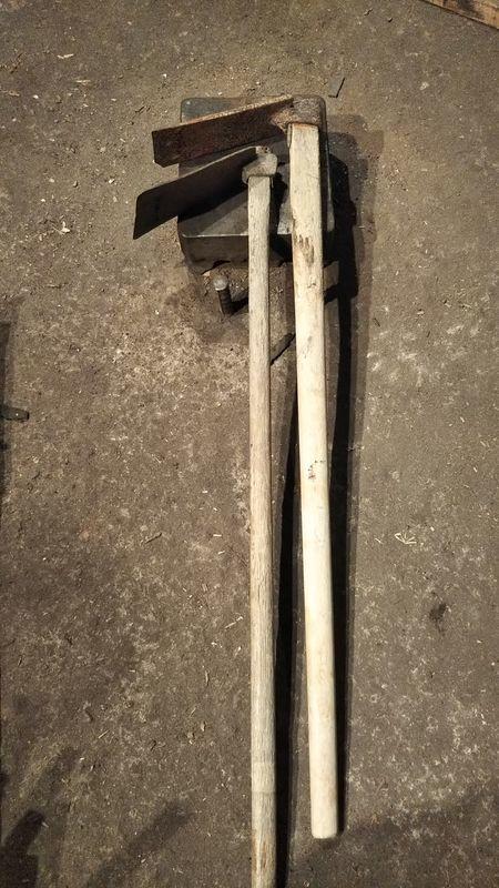 全体が入るように撮影された横向きに寝かせて並べてある柄の付いた板鍬と山鍬