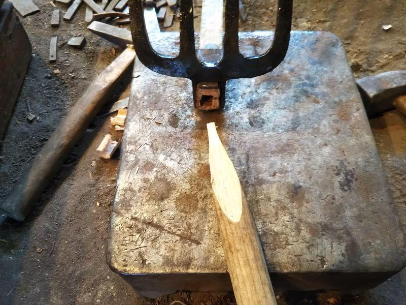 鍬に差してある柄に空いた穴と木の杭