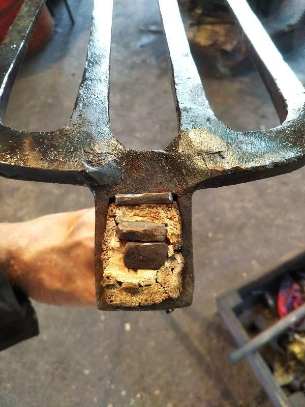 柄の穴に入れた木の杭の中に打たれた2本のクサビ