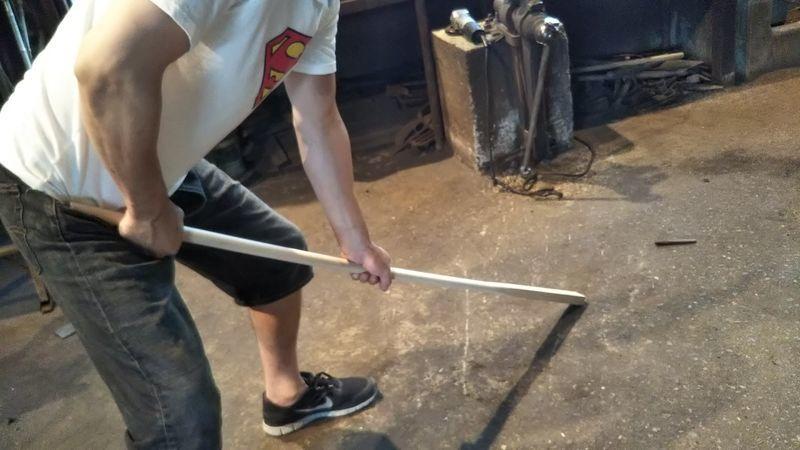 体重をかけて曲げられている鍬の柄