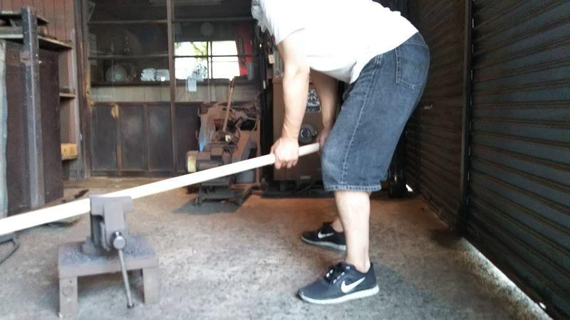 万力に挟んで体重を掛けられている鍬の柄