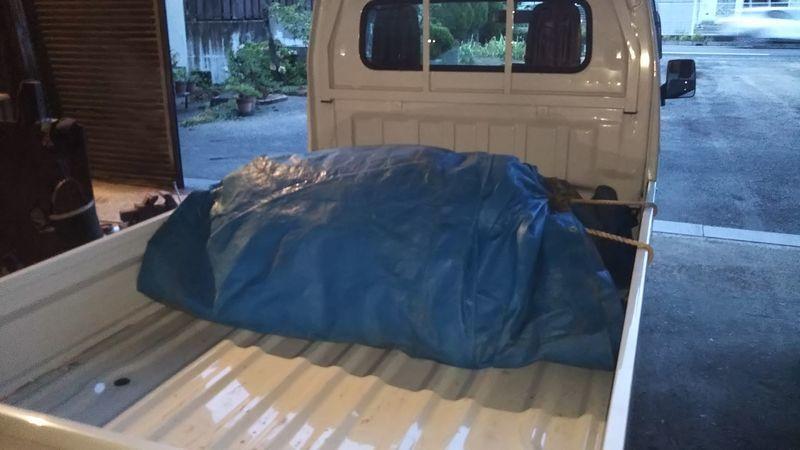 ブルーシートに巻かれた故障部分を載せた軽トラック