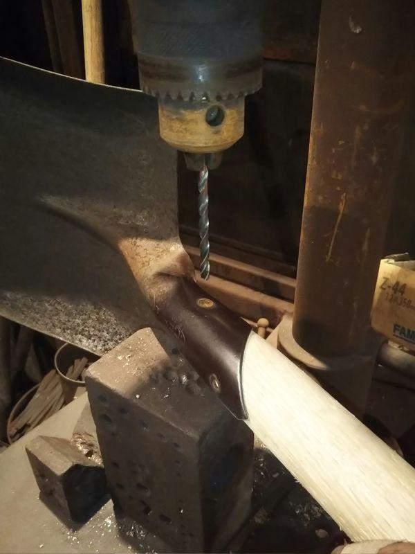 スコップ側面のリベットの穴を空けようとしているドリル