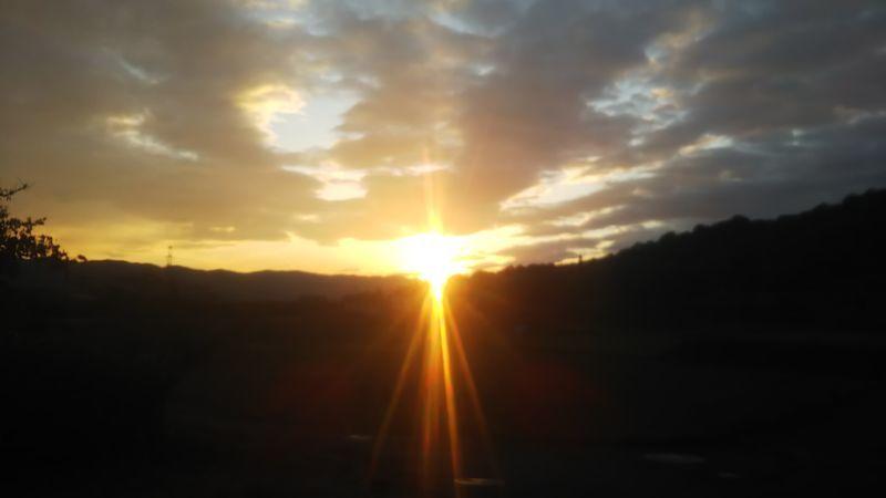 山の稜線を照らす夕日