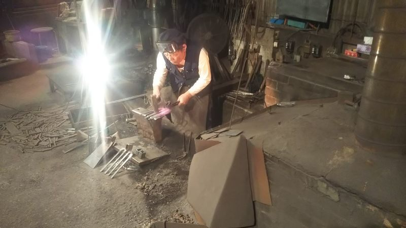 加熱した四つ鍬をハンマーで叩く鍛冶職人