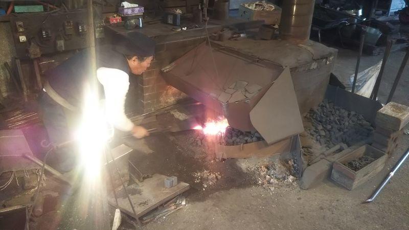 コークスの炎で板鍬を加熱する鍛冶職人