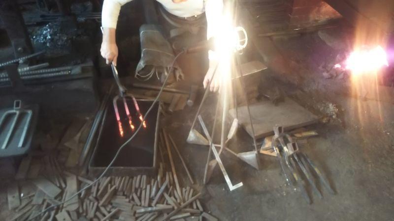 加熱した三つ鍬に焼き入れする鍛冶職人