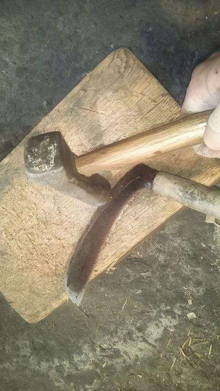 ハンマーで叩かれる木の台の上に置かれた草鎌