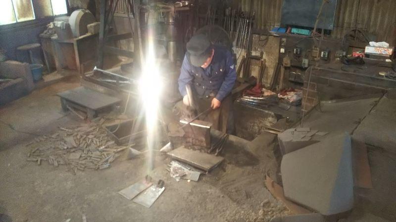 丸棒をハンマーで叩く鍛冶屋