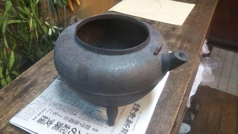 台の上に置かれた取っ手のない茶釜