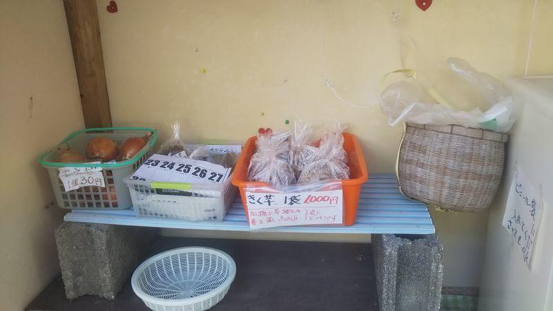 無人市場の中でそれぞれかごに入れて置かれたタマネギやきく芋
