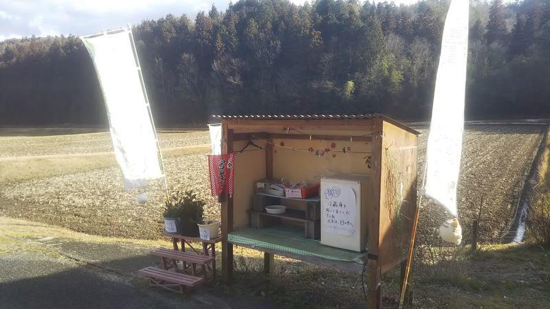 山間の道路脇に設置された野菜や漬け物を販売している無人市場