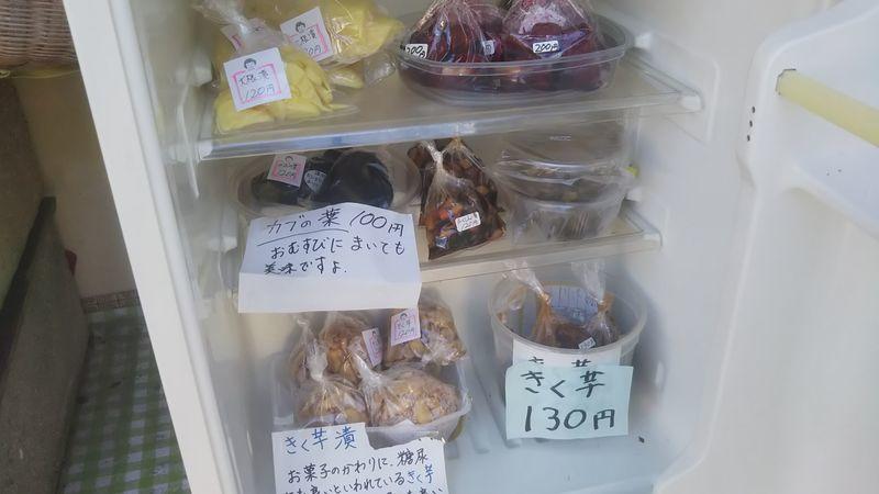 扉の空いた冷蔵庫の中に小袋に入れられたいろいろな種類の漬け物の入っている