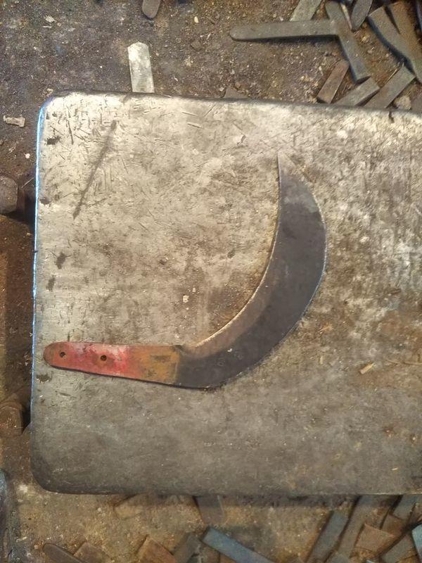 台の上に置かれた柄の付いていない錆びた鎌