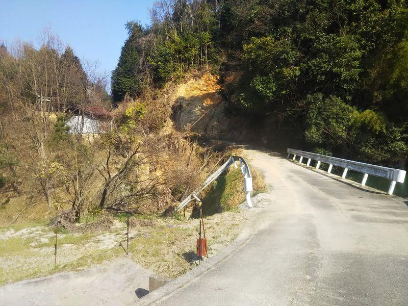 土砂崩れで塞がれた道路と折れ曲がったガードレール