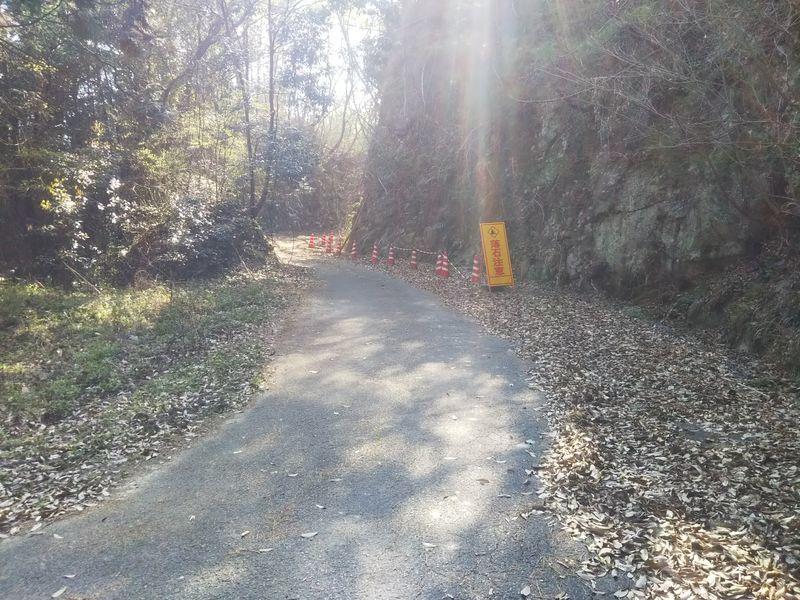 崖下の道路脇に置かれた落石注意の看板