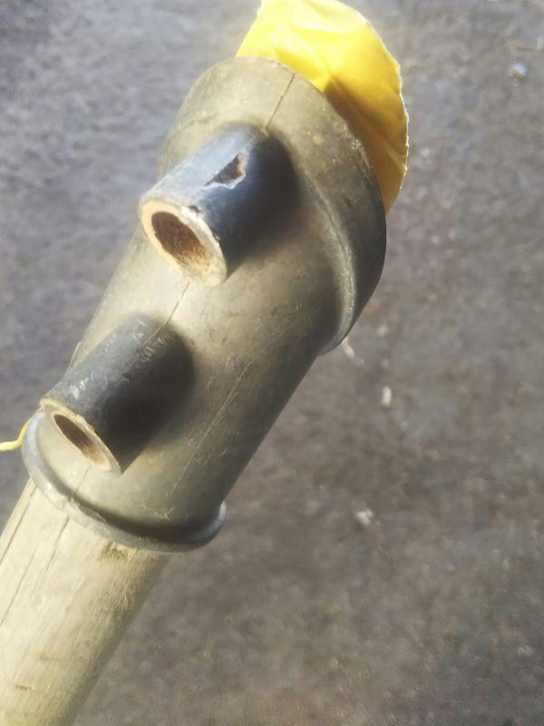 マスキングテープを巻かれた鋤簾の柄に軽くはめ込まれた金具