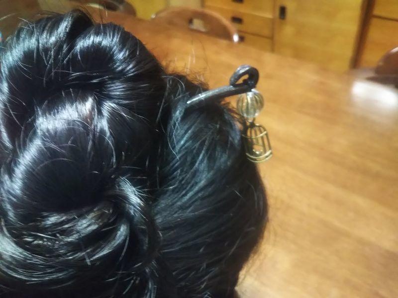 女性の髪に挿されたプラスチックの玉と鳥かごの形をした飾りをつけた金属製のかんざし