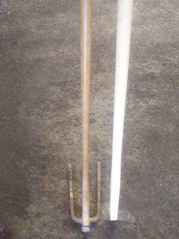 長年の使用で柄が細くなった三つ鍬の横に並べられた新品の鍬の柄