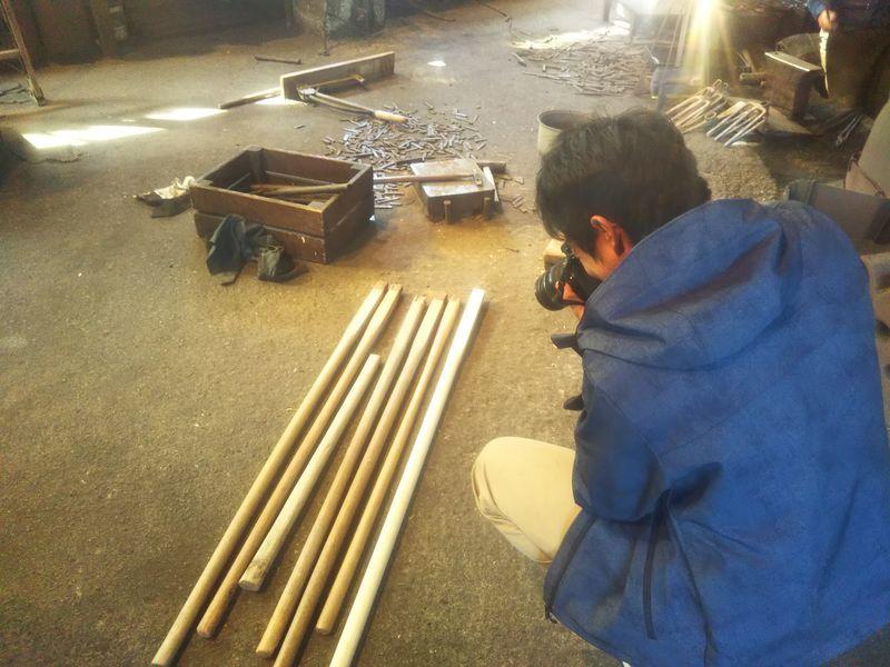 鍬の柄の写真を撮る男