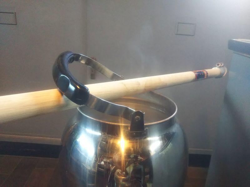 蓋の開いたヤカンから出る水蒸気によって蒸された鋤簾の柄