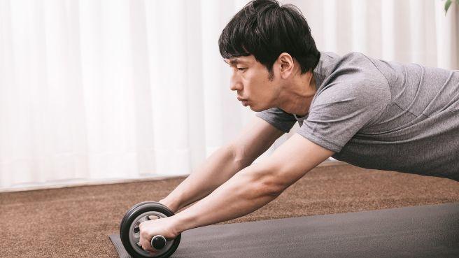 腹筋ローラーで筋トレをする男性の画像