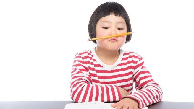 勉強に集中できず鉛筆を弄ぶ少女の画像
