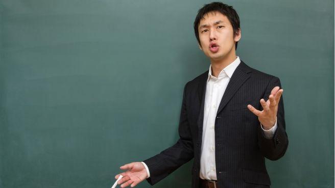 黒板の前で熱弁をふるう男性講師の画像