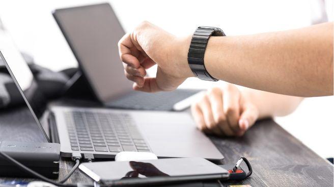 パソコンで作業中に腕時計を確認する人