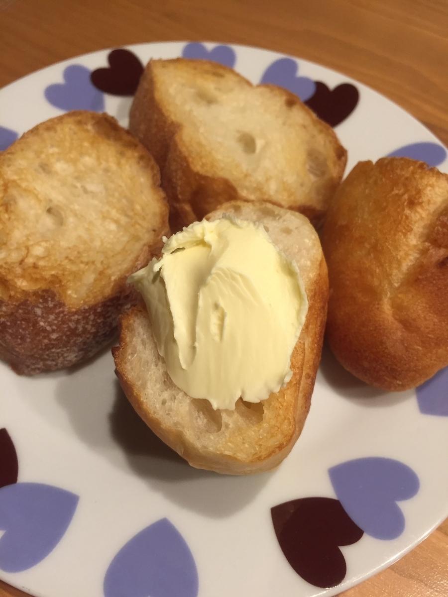 東京都町田市のアンテンドゥで購入したフランスパンを自宅でカットして焼いた後にバターを塗った写真