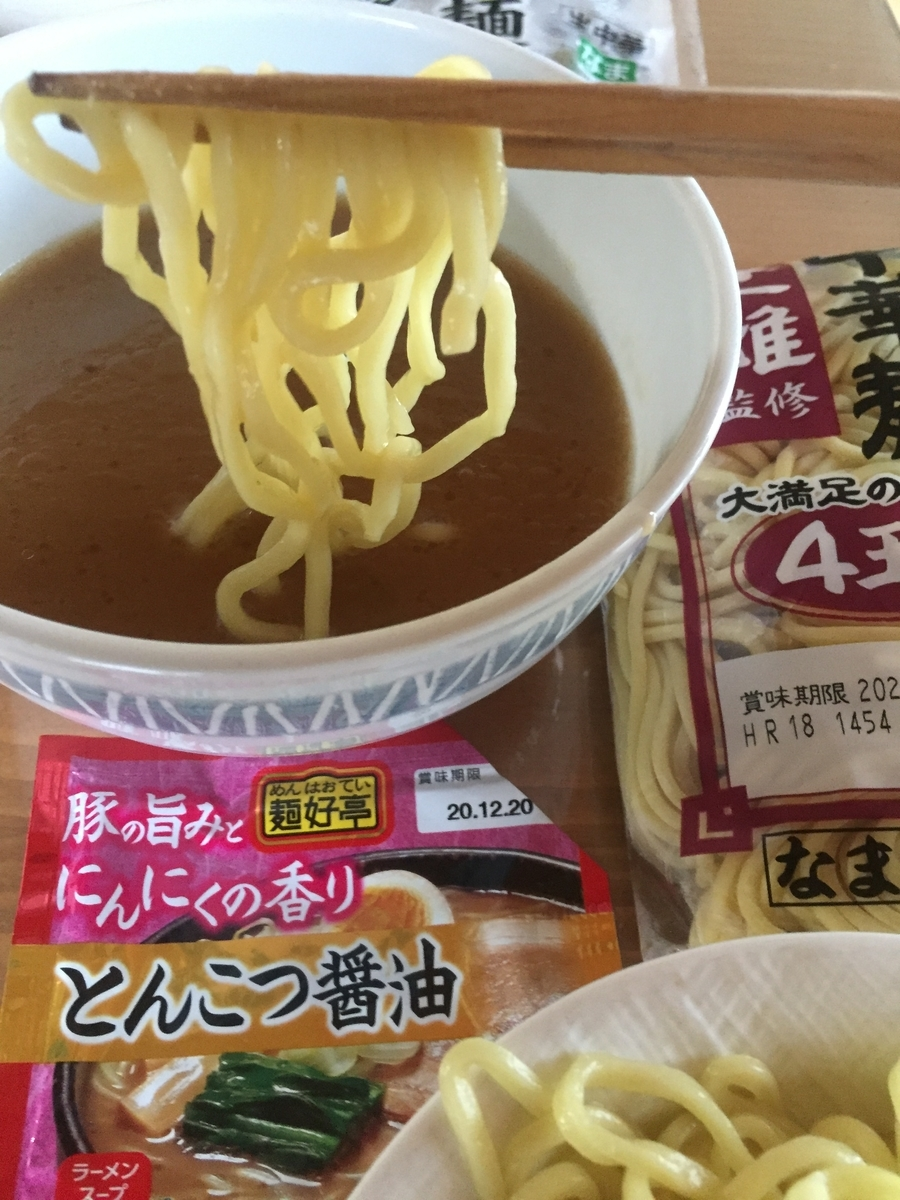 極太麺にとんこつ醤油を絡めて食べる様子を撮影した写真
