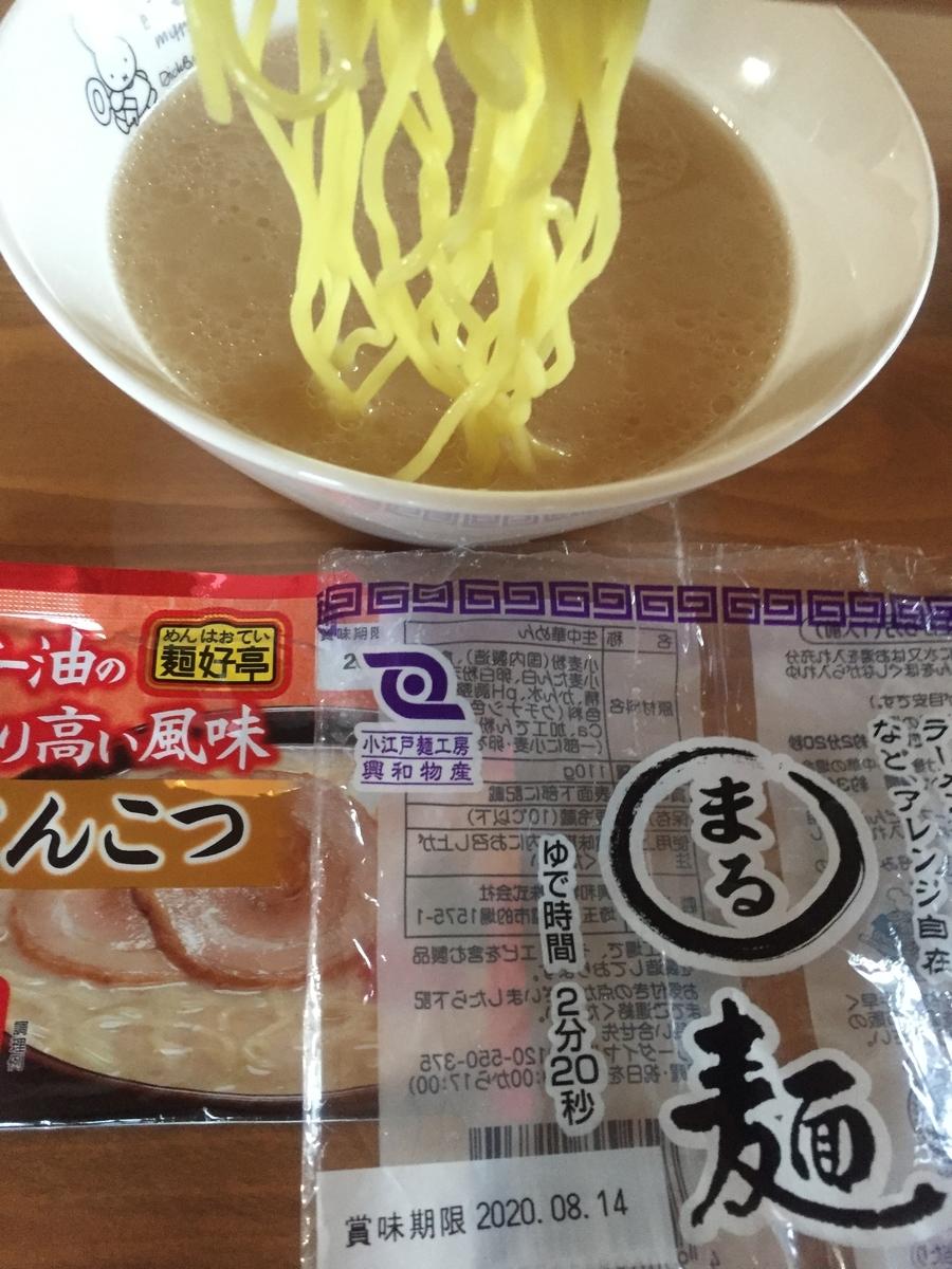 まる麺にとんこつスープを絡めて食べる様子を撮影した写真