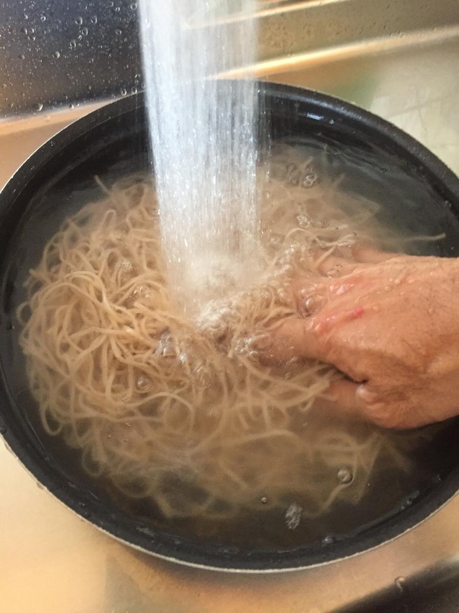 町田市根岸町にあるスーパー三和「アメリア三和町田根岸店」で購入したおびなた社の「生八割蕎麦」を茹で上げて、流水で滑りを洗い流している写真