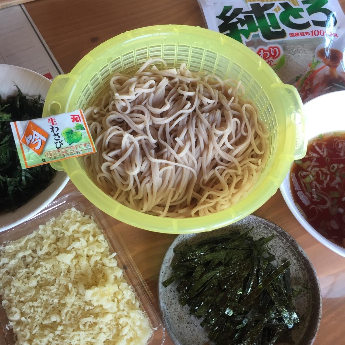 ざるそばの食べ方の紹介としてたくさんの様々な具材と一緒に乾麺のそばを中心に置いて撮影した写真