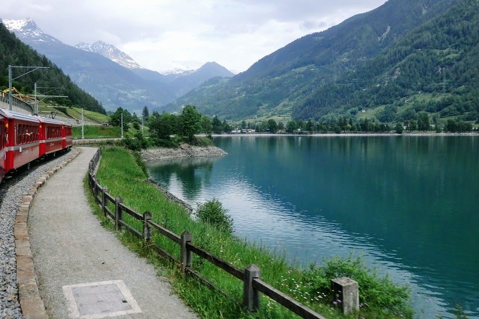 ポスキアーヴォ湖畔を走るベルニナ鉄道とアルプス山脈