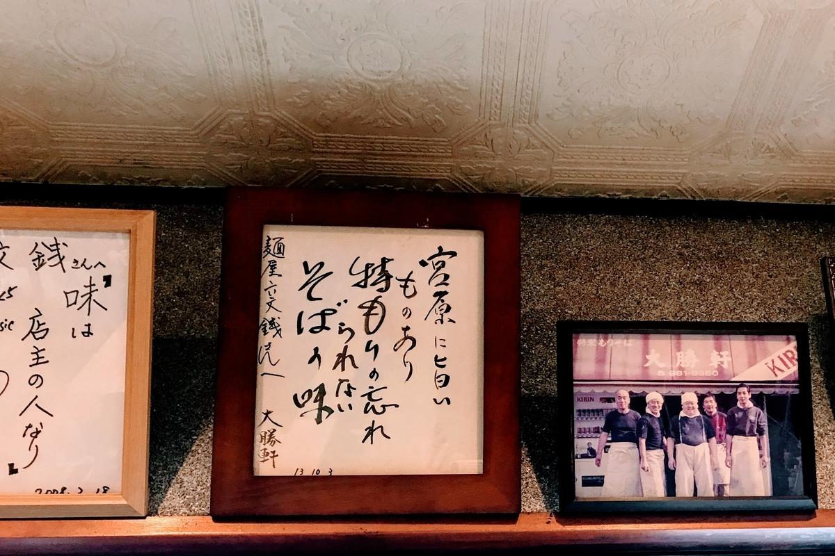 入り口から六文銭を見守る山岸一雄氏の色紙と六文銭店主との笑顔の写真
