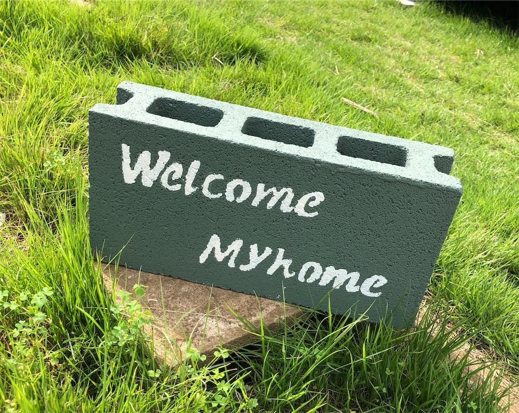 Wellcome Myhomeと書かれたコンクリートブロック。無塗装のコンクリートブロックの上に置いて飾った図。グリーンの芝生の上。