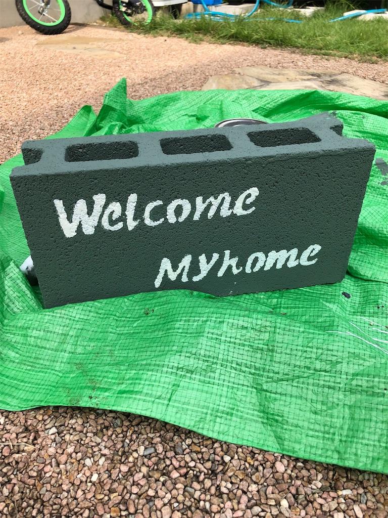 Wellcome Myhomeと書かれたコンクリートブロック。シートの上。