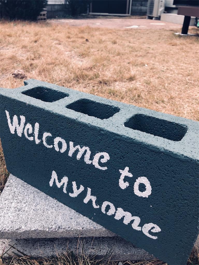 Well come to Myhomeと書かれたコンクリートブロック。茶色い芝生の上。