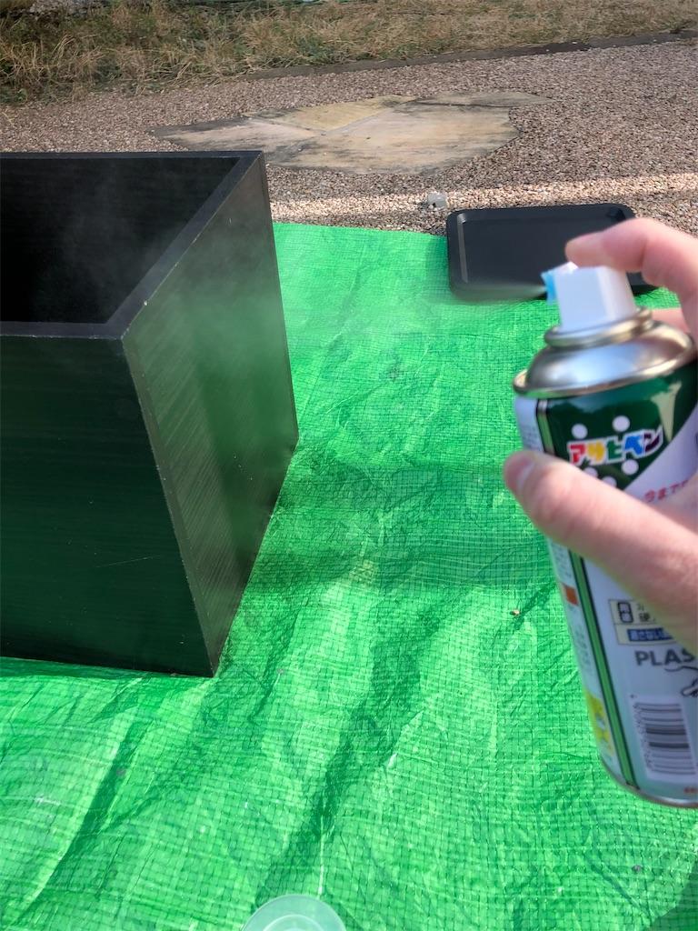 プラスチック用プライマーを黒いカラーボックスにスプレーする図
