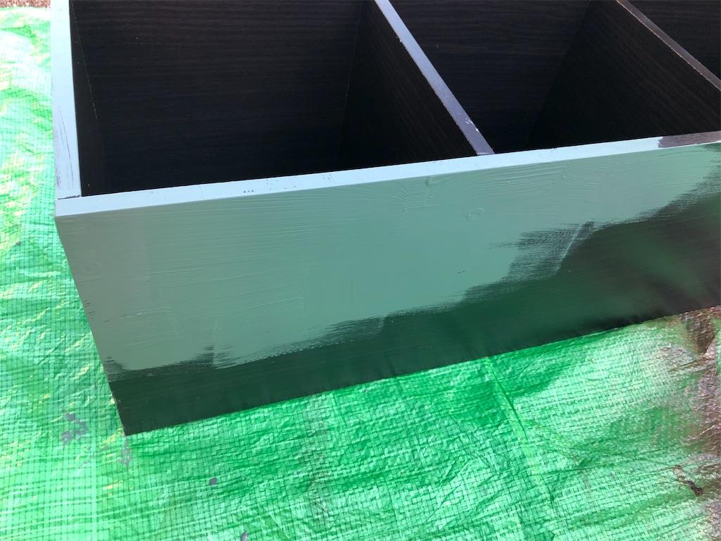 黒いカラーボックスにグリーンペンキを塗っている途中の図
