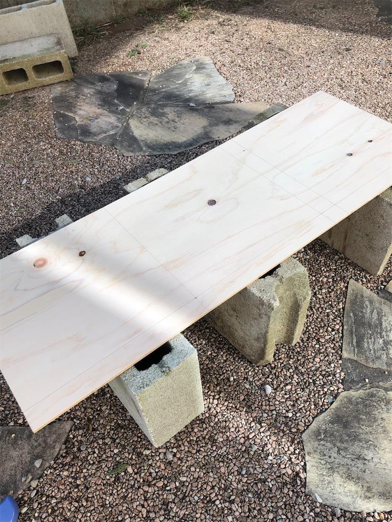 コンクリートブロックの上に置かれた合板。カット前