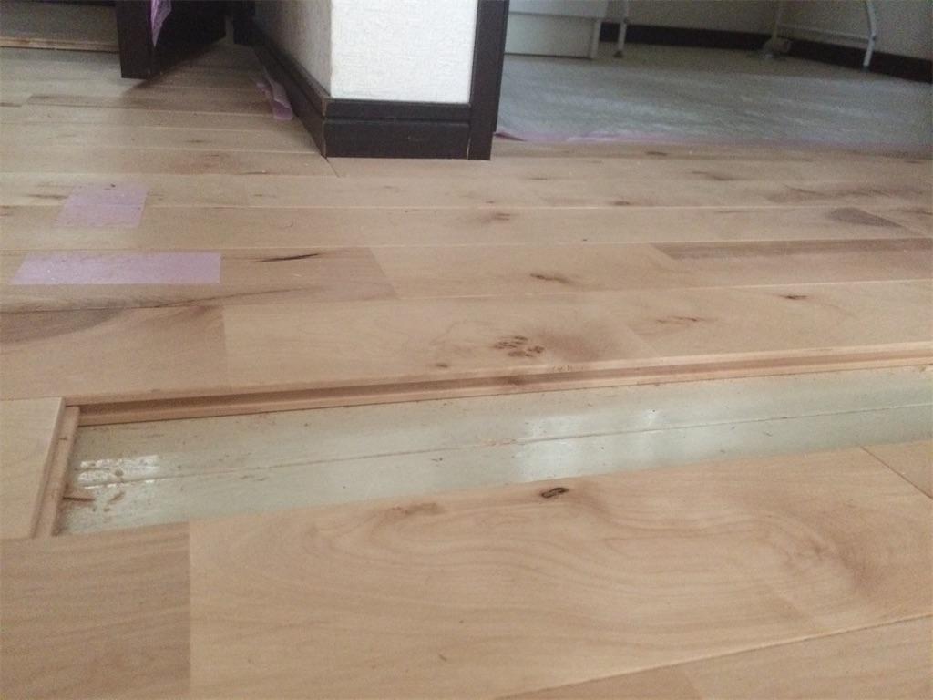 床のリフォーム途中の図。白いフローリングの上に無垢材の羽目板を貼っている図