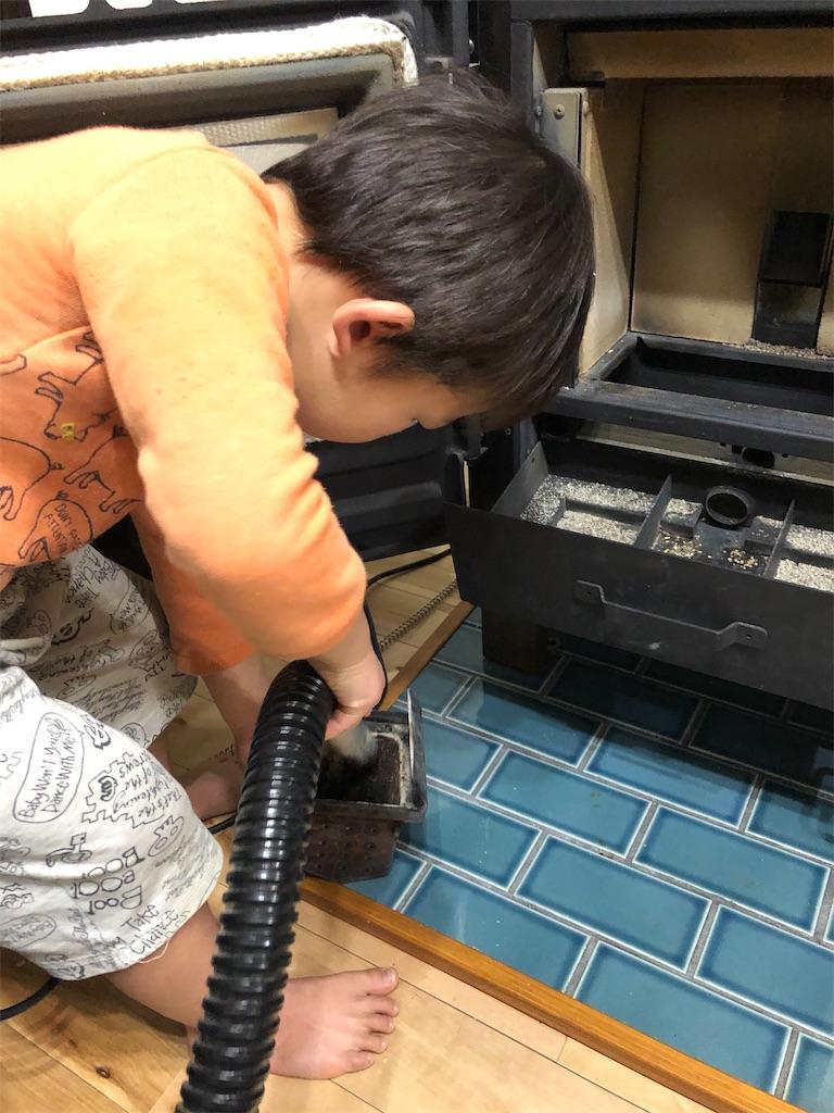 ペレットストーブの燃焼ポットに溜まった灰を掃除機で吸い込む子供