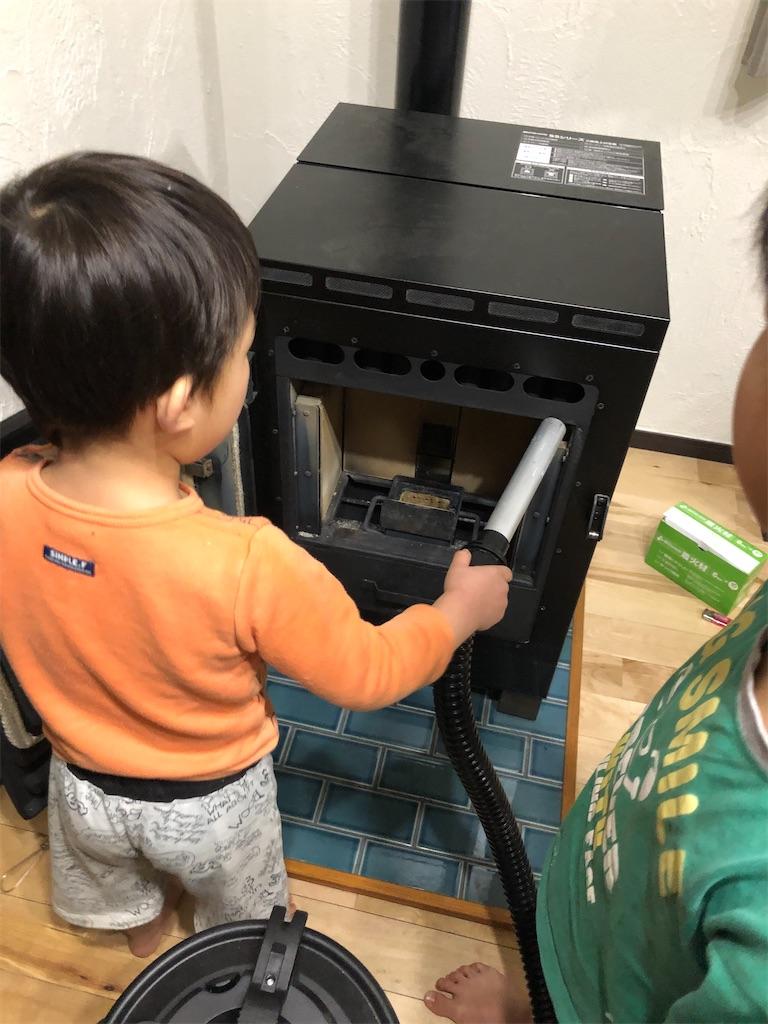 ペレットストーブを掃除する子供