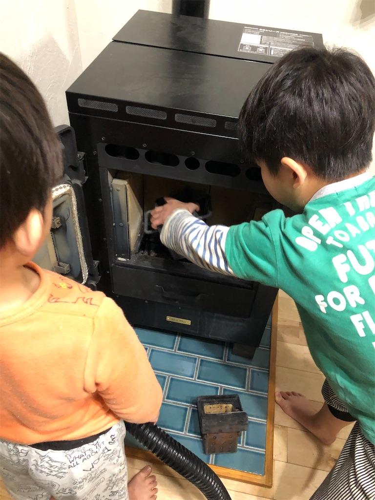 ペレットストーブの燃焼ポットなどの部品を外している子供2人
