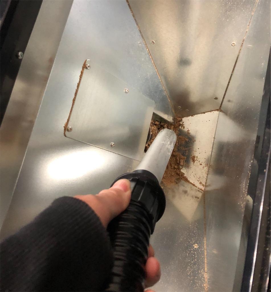 燃料タンクの中の木くずを掃除機で吸い込んでいる図